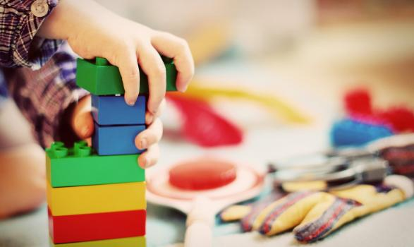 Child playing with coloured construction bricks