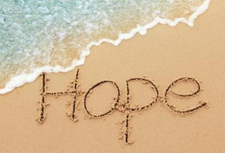 Sea and sand with word HOPE carved into sand